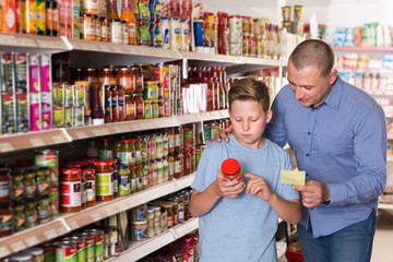 Father and son looking goods with shopping list in supermarket