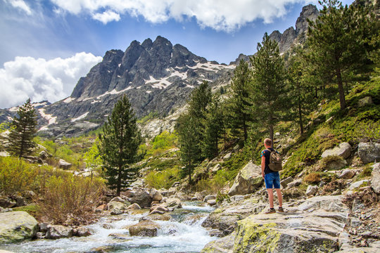 Man traveler with backpack hike across the river in Corsica natural park. Mountains, river and forest in the background.