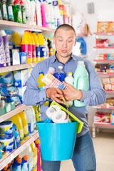 Man looking at shopping list of household detergents