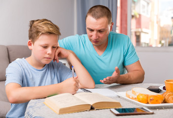 Adult male is helping his son are writing homework