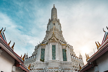 Vew of Wat Arun Buddhist temple during bright sunny day with sunset in the background, Bangkok, Thailand
