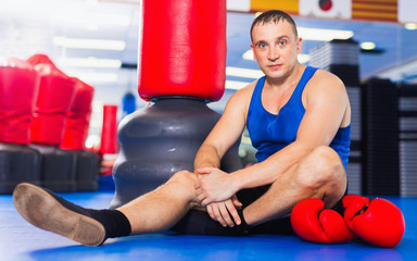 Man boxer is resting on the floor after training in gym.