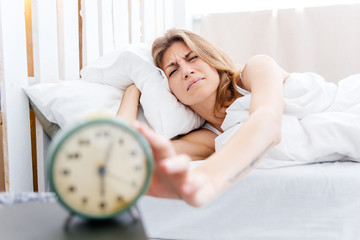 Young woman turns off the alarm clock in the morning