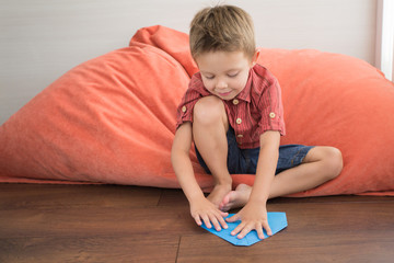 The boy at home sits on the floor and makes hand-made paper.