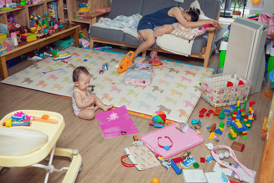 baby girl crying on the floor surrounded by toys
