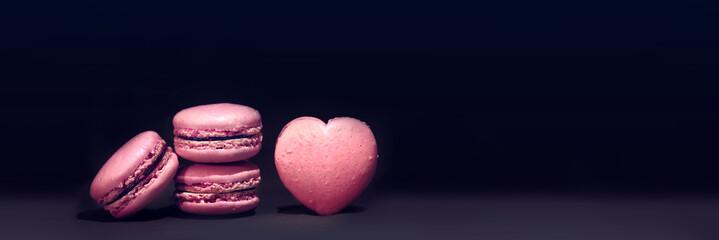 Foto auf Acrylglas Macarons macaron rose sur fond noir,pâtisserie