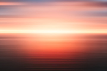 Abstract sunrise background of sea and cloudy sky over it. Motion blur sea water and red sky with clouds.