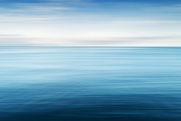 Abstract background of blue sea and cloudy sky over it. Motion blur sea water and sky with white clouds. Wall mural
