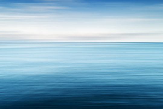 Abstract background of blue sea and cloudy sky over it. Motion blur sea water and sky with white clouds.