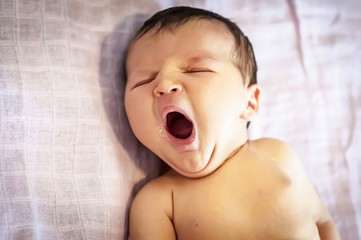 Funny newborn baby girl yawning with a trace of mother milk on her lips. Breast feeding baby concept, breastfeeding. Sleepy infant fall asleep.