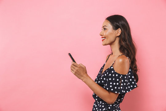 Side view of Happy brunette woman in dress holding smartphone