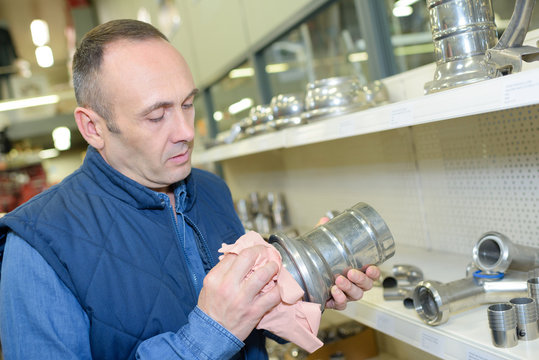 man cleaning metal oject for inspection