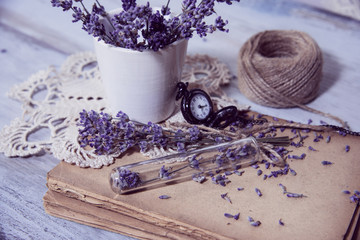 Time measuring clock old books and lavender flowers.