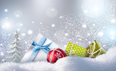 Concept of Christmas. Christmas colorful gifts, ball and Christmas tree fir on snow in winter snowdrift on silvery sparkling background with falling snow and copy space.