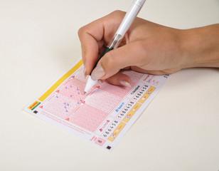 hand hält kgelschreiber und tippt lotto und füllt lottoschein aus kreuzchen ankreuzen jackpot