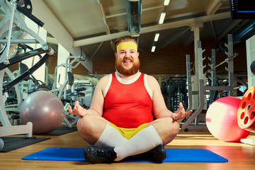 Funny fat man with a beard doing yoga in the gym.