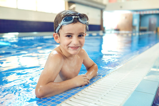 Little boy smiling child smiling at swimming pool indoors.