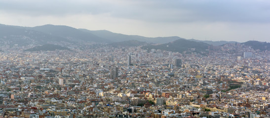 View to Barcelona city from the top of the Montjuic hill in cloudy day with bursts of sunlight. Barcelona skyline under grey clouds.