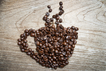 Coffee beans are cups and smoke on old wooden floor.