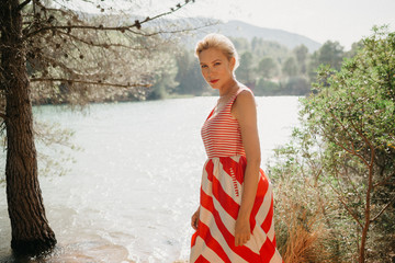 An attractive blonde woman in the red and white dress near the mountain lake. Spain