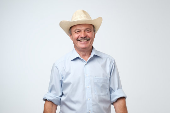 Cowboy style. Mature man adjusting his cowboy hat and laughing on joke while standing against grey background. Positive