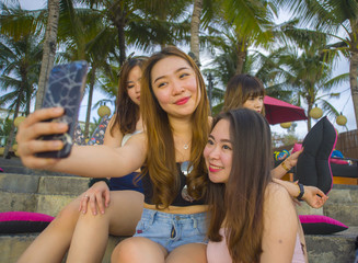 group with young happy and attractive Asian Chinese and Korean women hanging out , girlfriends enjoying holidays trip in tropical resort taking selfie picture with mobile phone