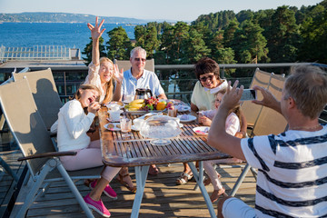 Big happy family having breakfast outdoors on terrace together, sitting around table, drinking coffee. Father taking picture on phone. Beautiful sea view, warm summer morning. Family portrait.