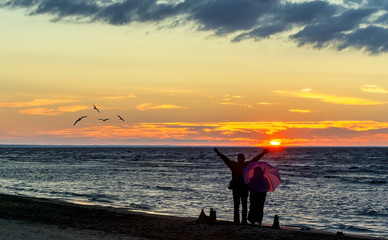 Happy people walking during sunset at a sandy beach of Jurmala - famous international Baltic resort in Latvia, Europe