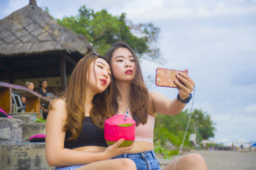 two young happy and attractive Asian Chinese and Korean women hanging out , girlfriends enjoying holidays trip in tropical resort taking selfie picture with mobile phone