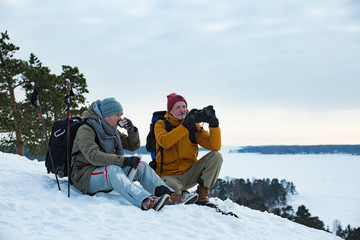 Two mature men exploring Finland in winter. Hikers sit on top of rock, take pictures with camera, drink hot coffee from thermos flask. Northern landscape with frozen Baltic Sea and snowy islands.