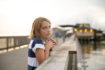Annoyed Child Tween Girl on Pier Looking at Parent to Stop taking Pictures