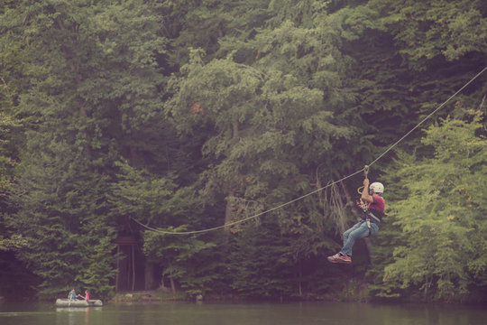 Zipline is an exciting adventure activity. Man hanging on a rope-way.