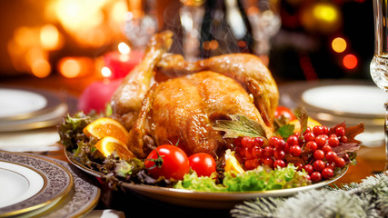 Hot tasty chicken from oven on dining table against burning fireplace