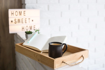 A cup of coffee and an open notebook on a wooden tray in the bright interior of the apartment. Home sweet home written on a decorative frame