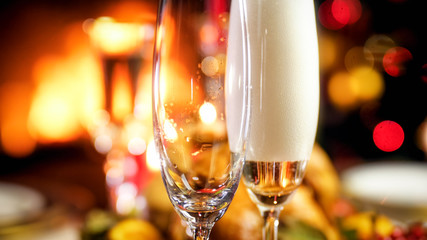 Closeup image of two glasses being filled with champagne