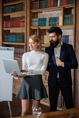 Reading concept. Sensual woman and handsome hipster reading ebook in library. Students update online reading material. Pretty girl and bearded man with laptop in reading room