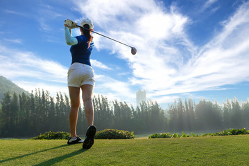 Asian woman golf player doing golf swing tee off on the green evening time in the blue sky background.  She presumably does exercise. Healthy and Lifestyle Concept.