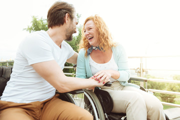 Laughing out loud. Low angle shot of positive minded woman and man grinning broadly while sitting in their wheelchairs and joking.
