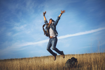Young happy man jumping into the air in the meadow