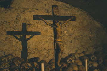 Decorated skulls in the Parish Church. Vintage candlesticks and crucifix casting shadows on the wall of the crypt
