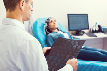 Detailed observation. Selective focus on a turned back laboratory worker examining a computed tomography scan while his female patient getting her brain analyzed by a electroencephalograph.