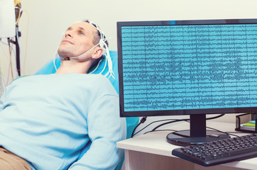 Modern medicine. Selective focus on a computer recording brain waves of a mature gentleman getting his brain analyzed by an electroencephalography machine.