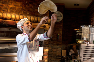 Zelfklevend Fotobehang Pizzeria Skilled chef preparing dough for pizza rolling with hands and throwing up