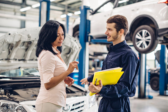 Auto car repair service center. The mechanic communicates with the client
