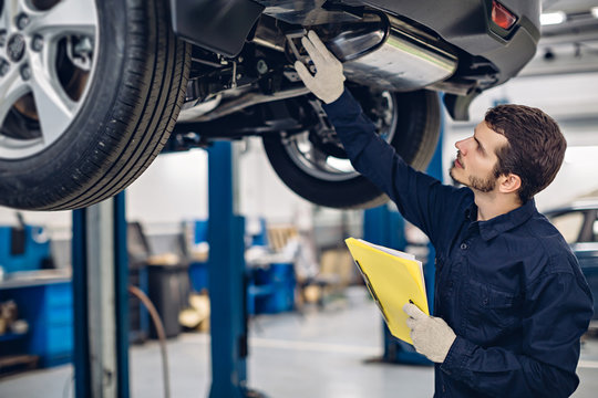 Auto car repair service center. Mechanic examining car