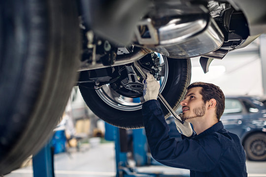 Auto car repair service center. Mechanic examining car suspension
