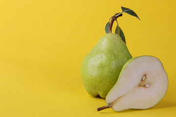 A fresh ripe pear and half a green pear on a bright yellow background with a place for an inscription