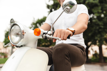 Cropped image of Young business man riding on retro scooter