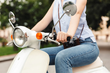Cropped image of young hipster woman riding on scooter