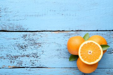 Orange fruit with green leafs on blue wooden table